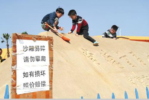 """""""沙雕易碎,请勿攀爬"""",可偏偏就有小孩子爬了上去,甚至拿着铲子破坏它."""